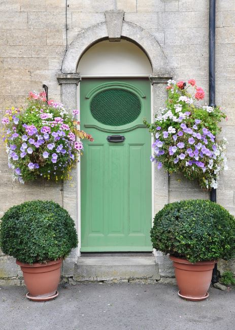 Spruce up your front porch by flanking the front door with beautiful decorative planters. Symmetry is important here; keep the right and left sides of the front door matching. This will add a sense of organization and a pop of color to your front porch.