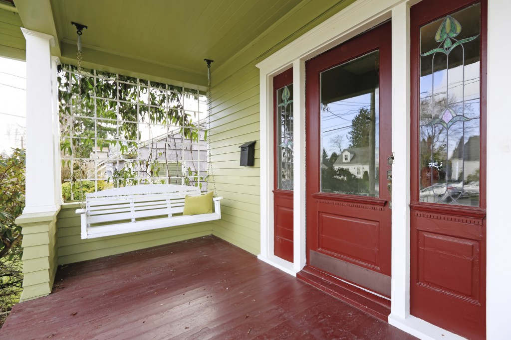 Entrance porch in red and green color with hanging swing